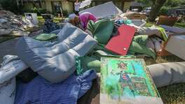 A painting (foreground) that hung in Catherine Sharpe's 8 -year-old son's (Jake) room, shows the water line mark on a painting put out for trash after the aftermath of Hurricane Harvey Thursday, Aug. 31, 2017, in Friendswood.
