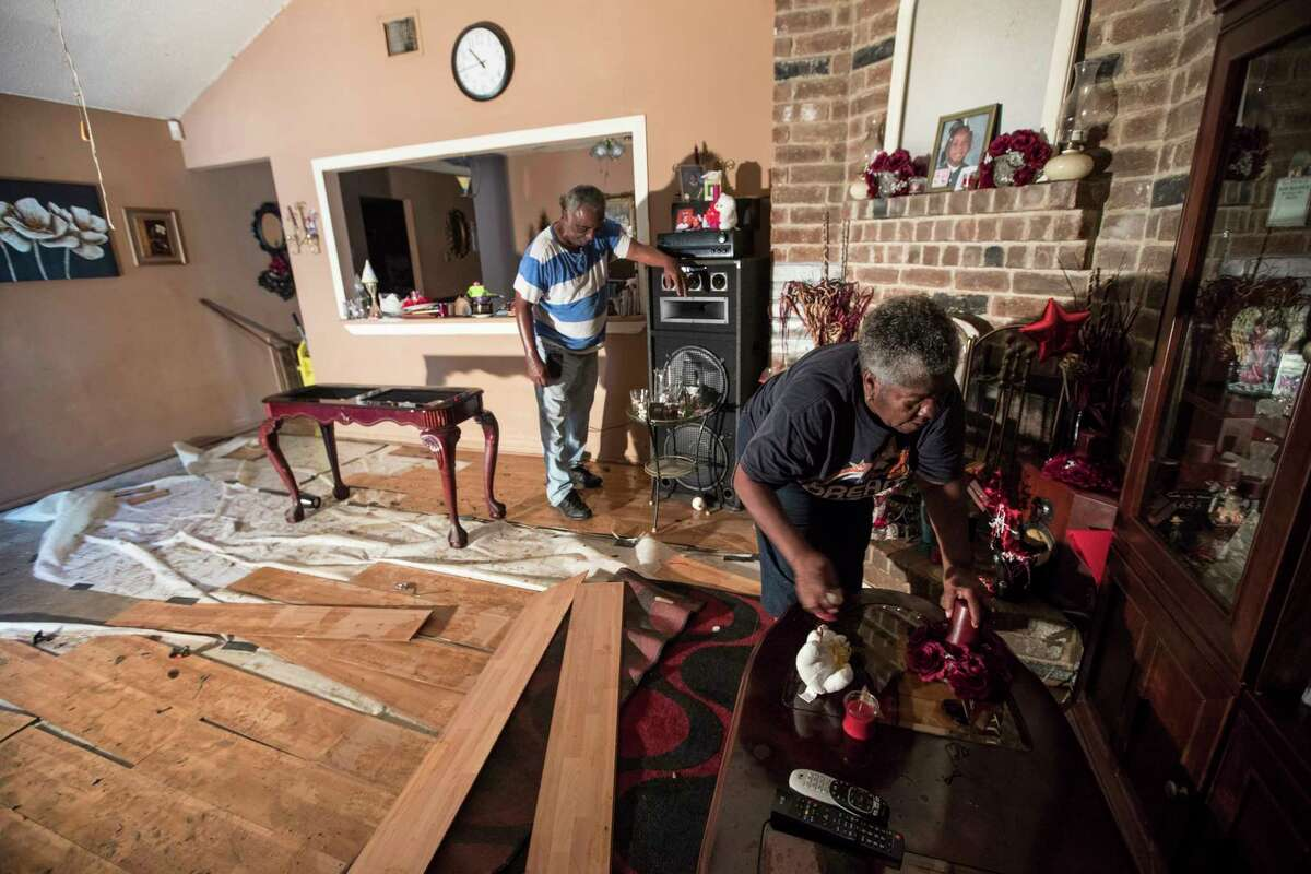 Willie Johnson, left, and his wife Loicy, clean up their flood-damaged home in the aftermath of Tropical Storm Harvey in the Verde Forest subdivision on Thursday, Aug. 31, 2017, in Houston.