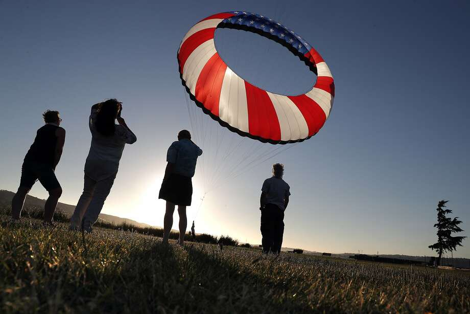Friends of Tony Jetland watch his American flag kite rise at Waterfront Park in Martinez in June. Photo: Carlos Avila Gonzalez, The Chronicle
