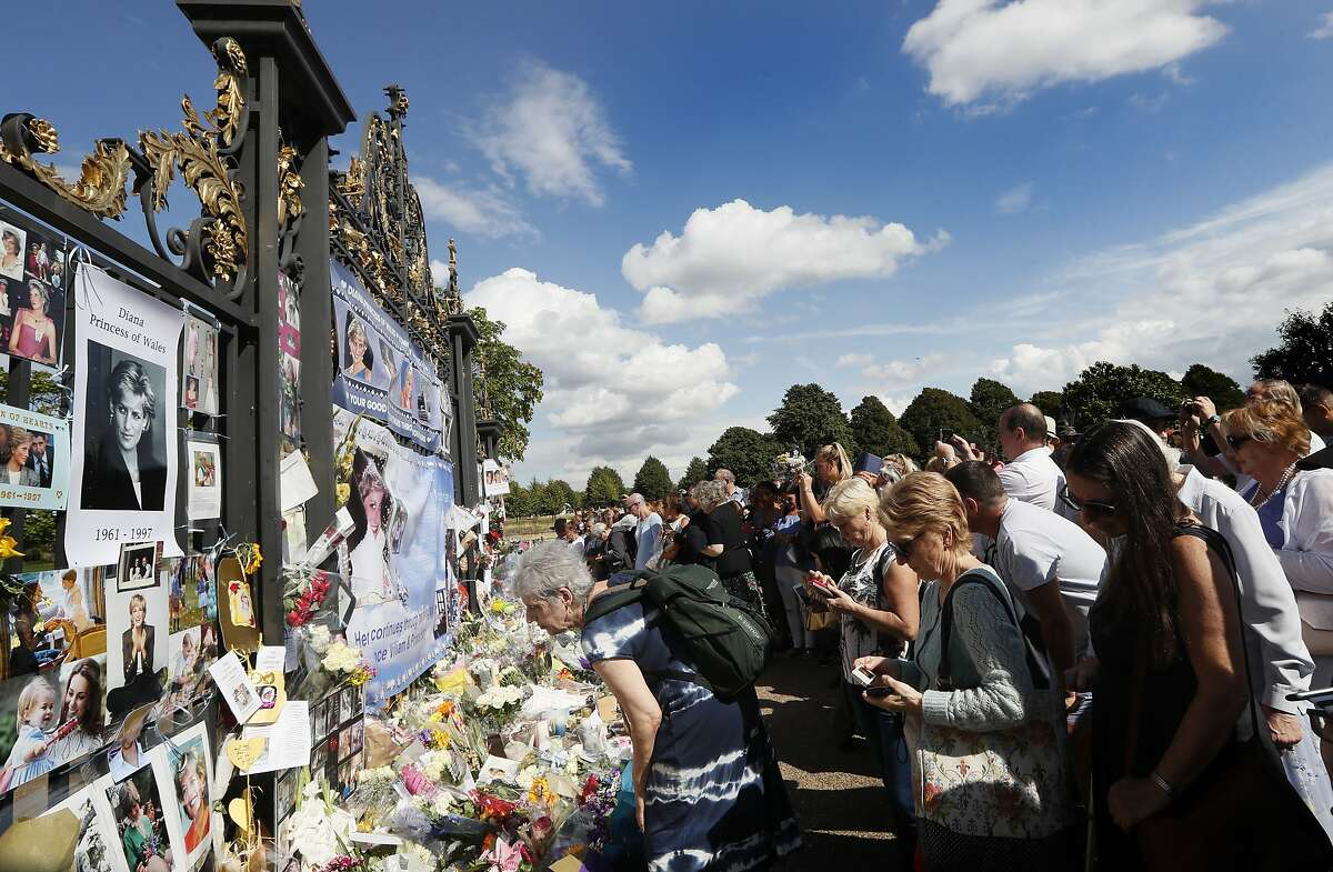 People crowd around the gates of Kensington Palace in London to pay tribute to the late Diana, Princess of Wales, Thursday, Aug. 31, 2017.