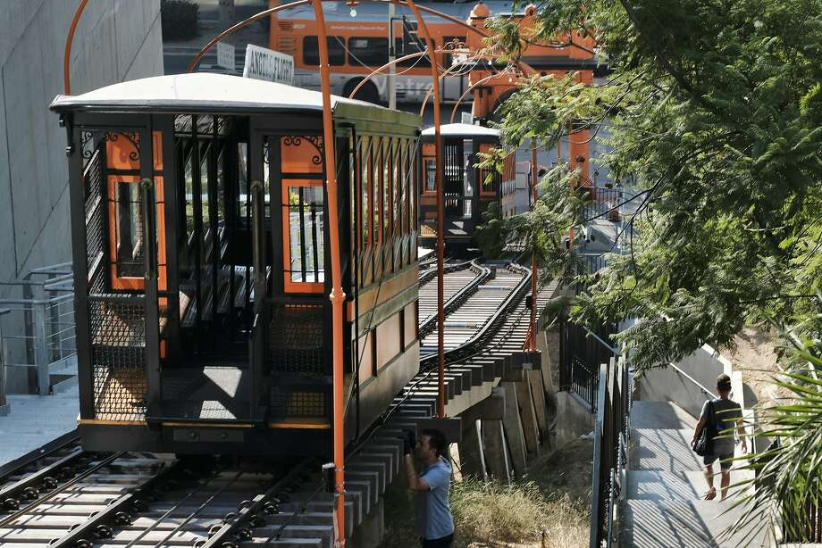 A pedestrian walks a steep flight of stairs next to the Angels Flight railroad as a worker makes final preparations for the reopening of the tiny railroad in downtown Los Angeles. Photo: Richard Vogel, Associated Press