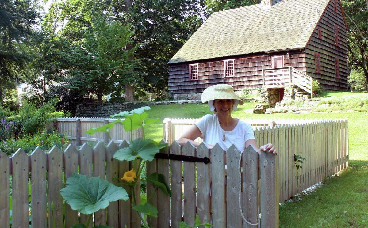Whitney Vose, a member of the Fairfield Garden Club, and docent for the Colonial Kitchen Garden at the Ogden House, stands at the gate to the garden, where plants that would have been grown by colonial women are cultivated.