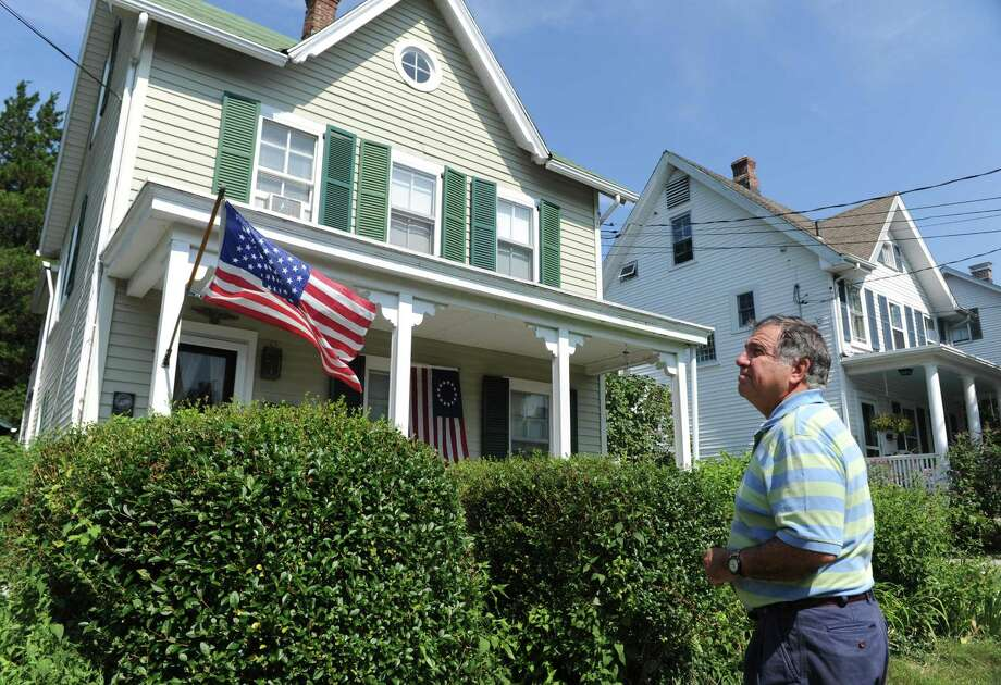 Dean Gamanos looks upon his home on Division Street in Greenwich, Conn. Thursday, Aug. 31, 2017. Gamanos's 1888 home is the Patrick O'Connor House, registered in the Greenwich Historical Society's Greenwich Landmarks Registry. The block is part of the Fourth Ward Historic District, with many homes showing a Queen Anne revival-style architecture. Photo: Tyler Sizemore / Hearst Connecticut Media / Greenwich Time