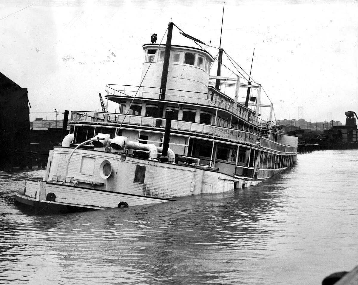 People watch , as Barney Gould's future showboat is sinking March 14, 1952 Photo ran 3/15/1952, P. 3