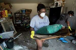 Menion Brock and Michelle Green clean up their home damages by floodwaters of Tropical Storm Harvey in the Parkway Forest subdivision on Thursday, Aug. 31, 2017, in Houston.