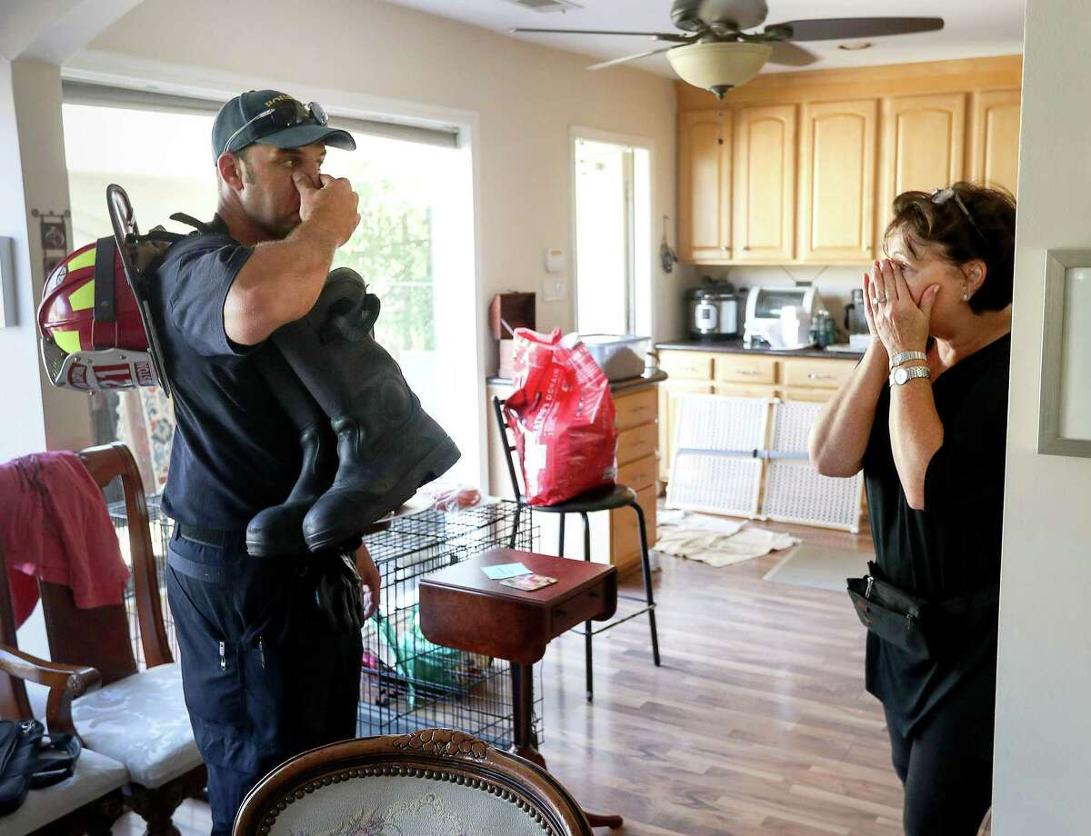 Sharlene Barris, right, tears up when she sees Houston Fire Capt. Joshua Vogel as he did home welfare checks in the Meyerland area Thursday. Vogel's team evacuated Barris and her husband as waters rose into their home.