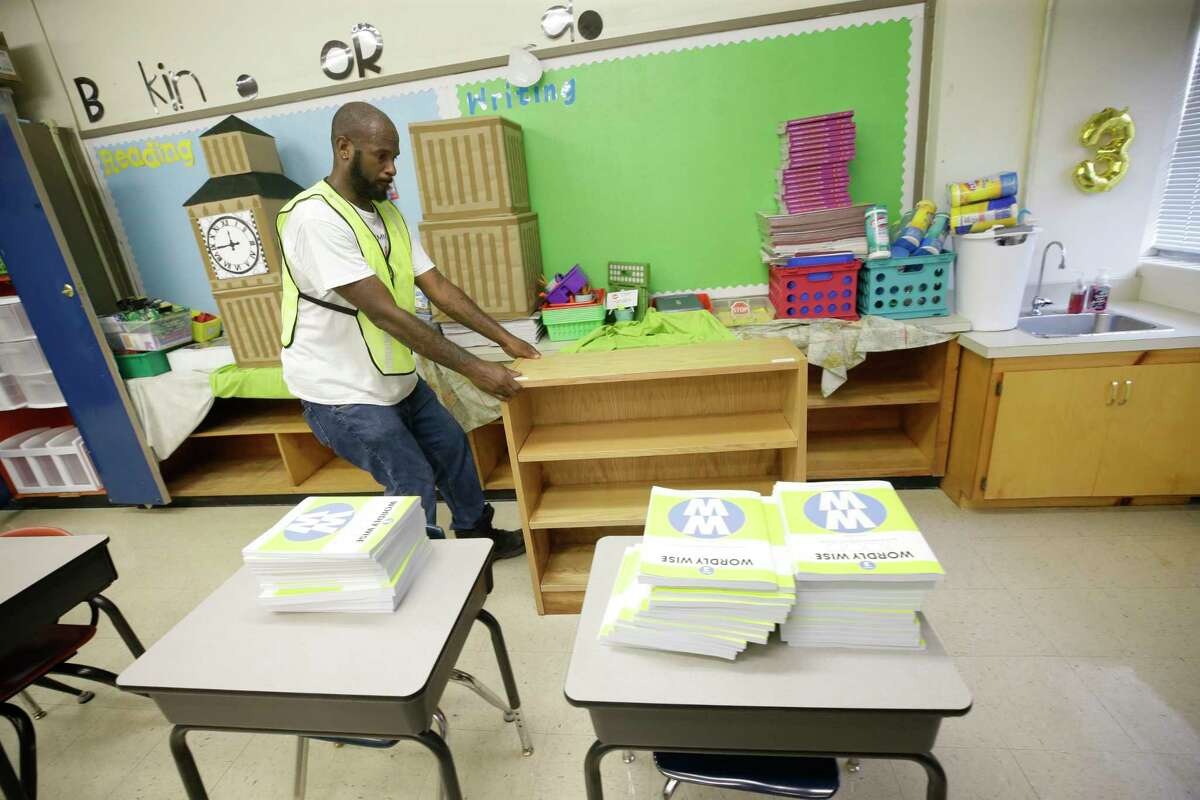 Deshawn Bonner pulls a wooden bookcase from a classrooms as crews clean at Kolter Elementary, 9710 Runnymeade Dr., Thursday, Aug. 31, 2017, in Houston. Many schools were damaged from flooding in the aftermath of Hurrican Harvey.