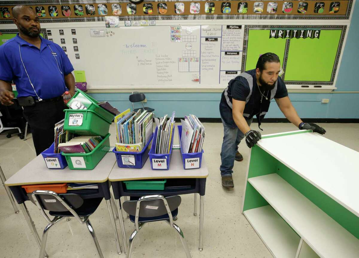Patrick Lawani, left, with Blackmon Mooring, and Albert Garcia, right, clear classrooms at Kolter Elementary, 9710 Runnymeade Dr., Thursday, Aug. 31, 2017, in Houston. Many schools were damaged from flooding in the aftermath of Hurrican Harvey.