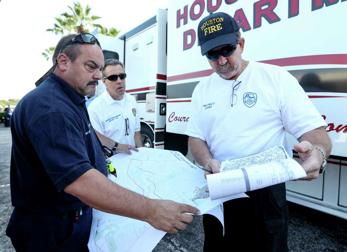 James Ingledue, with FEMA, from left, HFD District Chief Hunter Schappaugh, and District Chief Richard Cole, check maps before doing welfare checks on residents in the Meyerland area, Thursday, Aug. 31, 2017, in Houston.