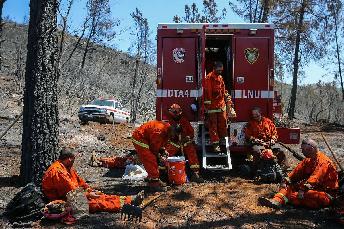 Inmates from the Delta Conservation Camp #8 break for lunch after looking for hot spots at the Canyon fire in Napa, Calif., on Tuesday, Aug. 15, 2017.