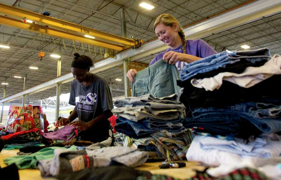 Willis head volleyball coach Megan Storms, right, shares a laugh with player De'Janae Gilmore as they sort and stack donated clothes at Falcon Steel's warehouse, Wednesday, Aug. 30, 2017, in Conroe. The company donated the space to serve as a central drop off location for donated supplies to help Montgomery County residents affect by Toprical Storm Harvey. Photo: Jason Fochtman, Staff Photographer / © 2017 Houston Chronicle