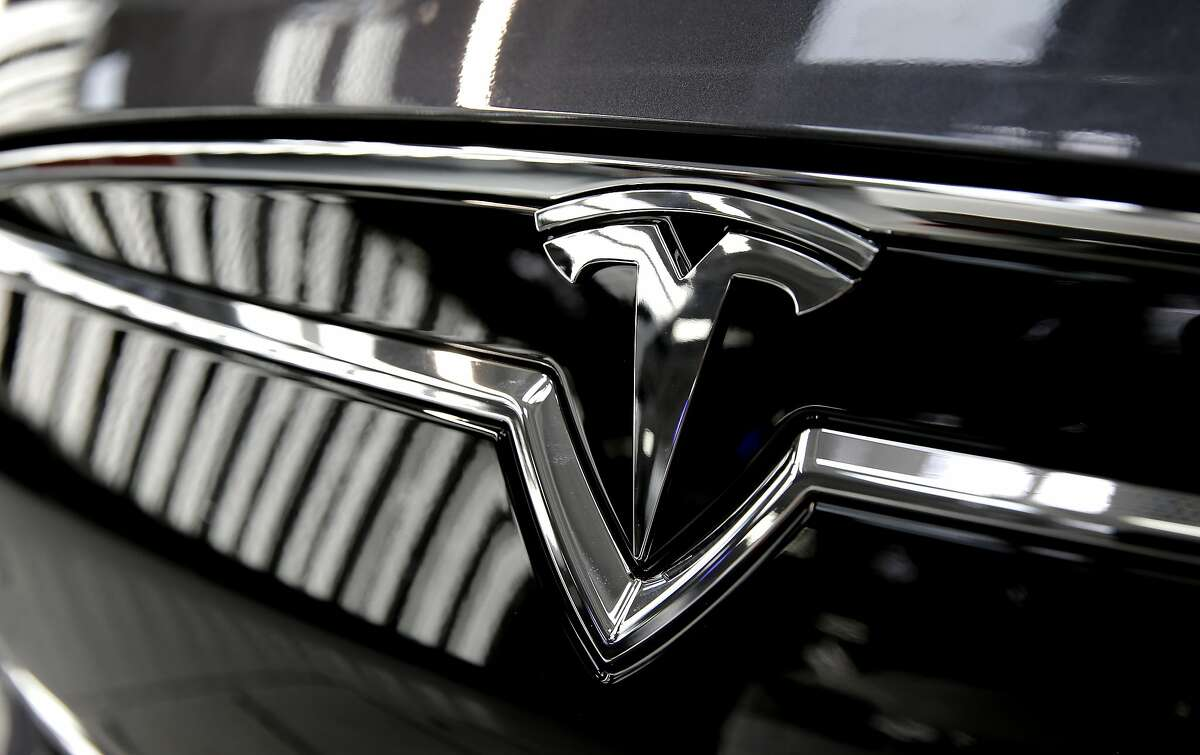 """A shimmering Tesla """"T"""" completes the front grill of the electric vehicle as it nears the end of the assembly line at Tesla Motors, California's only full-scale auto manufacturing plant, as seen on Thurs. Feb. 19, 2015, in Fremont, Calif."""