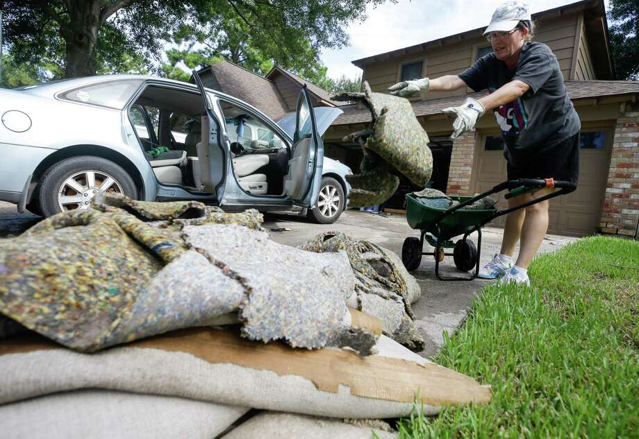 Susan Henney tosses wet carpet as she helps her neighbors clean up from flooding in the Lakewood Forest subdivision Wednesday, August 30, 2017 in Houston. Much of the Houston area was flooded in the aftermath of Hurricane Harvey. ( Melissa Phillip / Houston Chronicle) Photo: Melissa Phillip, Staff / Houston Chronicle 2017