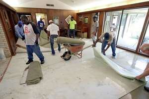 Workers remove carpet damaged by floodwaters from Tropical Storm Harvey from a home Wednesday, Aug. 30, 2017, in Houston. (AP Photo/David J. Phillip)