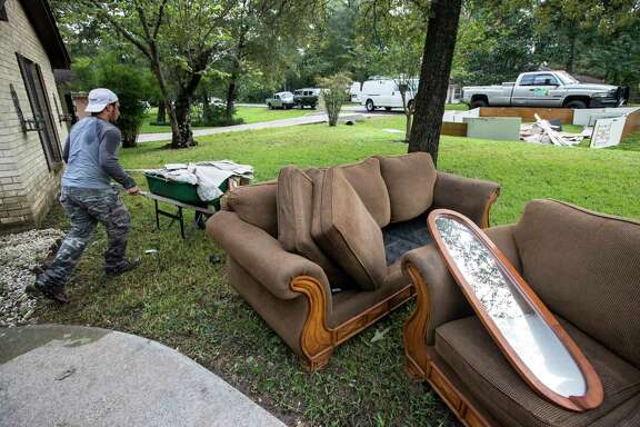 A construction crew cleans out the home of Kenny Licona, which was flooded out from Tropical Storm Harvey on Wednesday, Aug. 30, 2017, in Spring, Texas.    (Brett Coomer/Houston Chronicle via AP)