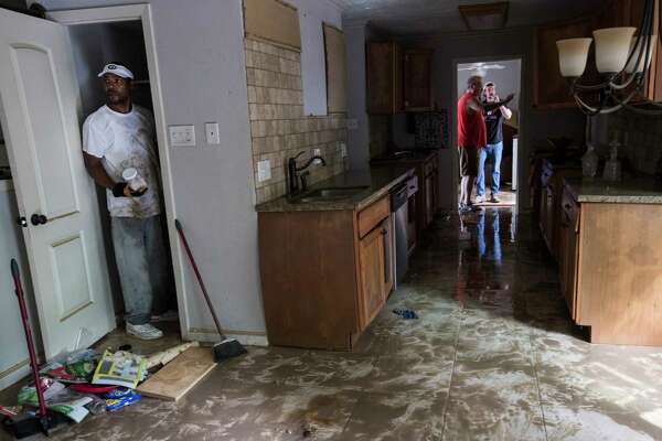 Craig Hardy helps clean out Michael Boyd's home, which was flooded with eight feet of water, in the aftermath of Tropical Storm Harvey on Wednesday, Aug. 30, 2017, in Houston. ( Brett Coomer / Houston Chronicle )
