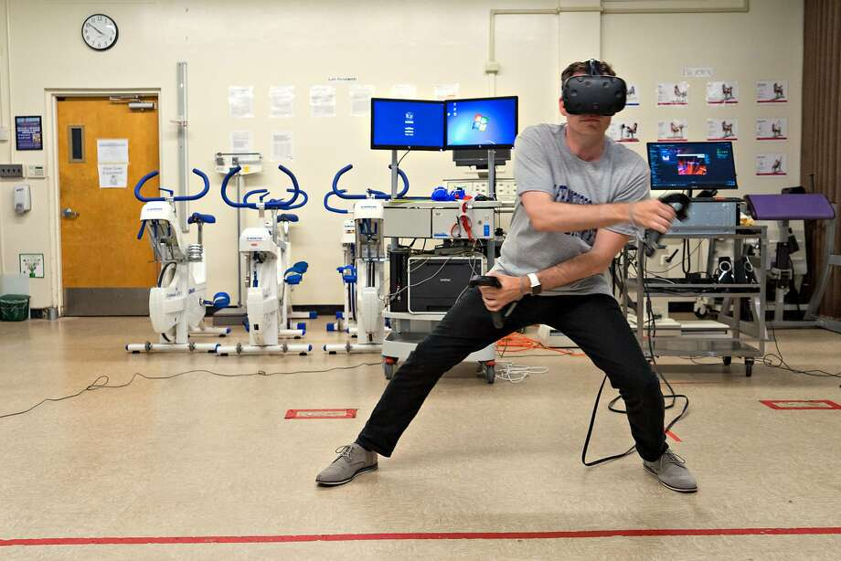 Aaron Stanton exercises using a virtual reality headset at San Francisco State University on Monday, Aug. 21, 2017. Researchers at the university are studying how effective exercising using virtual reality can be. detail caption; A Vive virtual reality headset is seen at San Francisco State University on Monday, Aug. 21, 2017. Researchers at the university are studying how effective exercising using virtual reality can be. Photo: James Tensuan, Special To The Chronicle