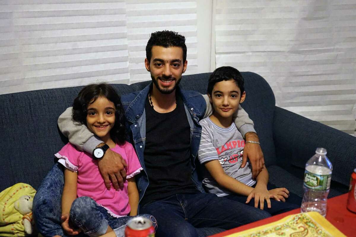 Safeih's children Mohammad, 10-year-old Omar and 7-year-old Haya Shanif sit together on the couch in their Albany apartment on August 30, 2017.