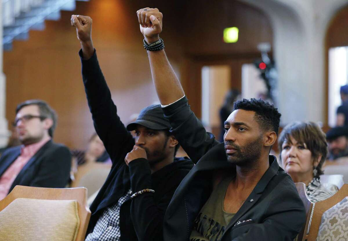 Mike Lowe (right) and Johnathan-David Jones raise their arms to show support for the removal and relocation of a Confederate statue from Travis Park on Thursday, Aug. 31, 2017. City Council voted 10-1 on the removal of a Confederate statue during an emotional session in chambers voiced by citizens and council members. Despite a few voices opposing the removal, the decision was near unanimous after nearly three hours of discussion on both sides of the dais. (Kin Man Hui/San Antonio Express-News)