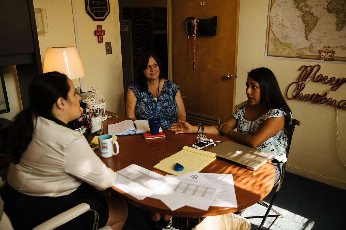 Legal Services Program Manager, Maciel Jacques, left, and Communication Director, Mary B. Kuhn, center, listen to Joseline Gonzalez, right, as she explains her fear of DACA ending at Catholic Charities of the East Bay in Oakland, Calif. Thursday, August 31, 2017.