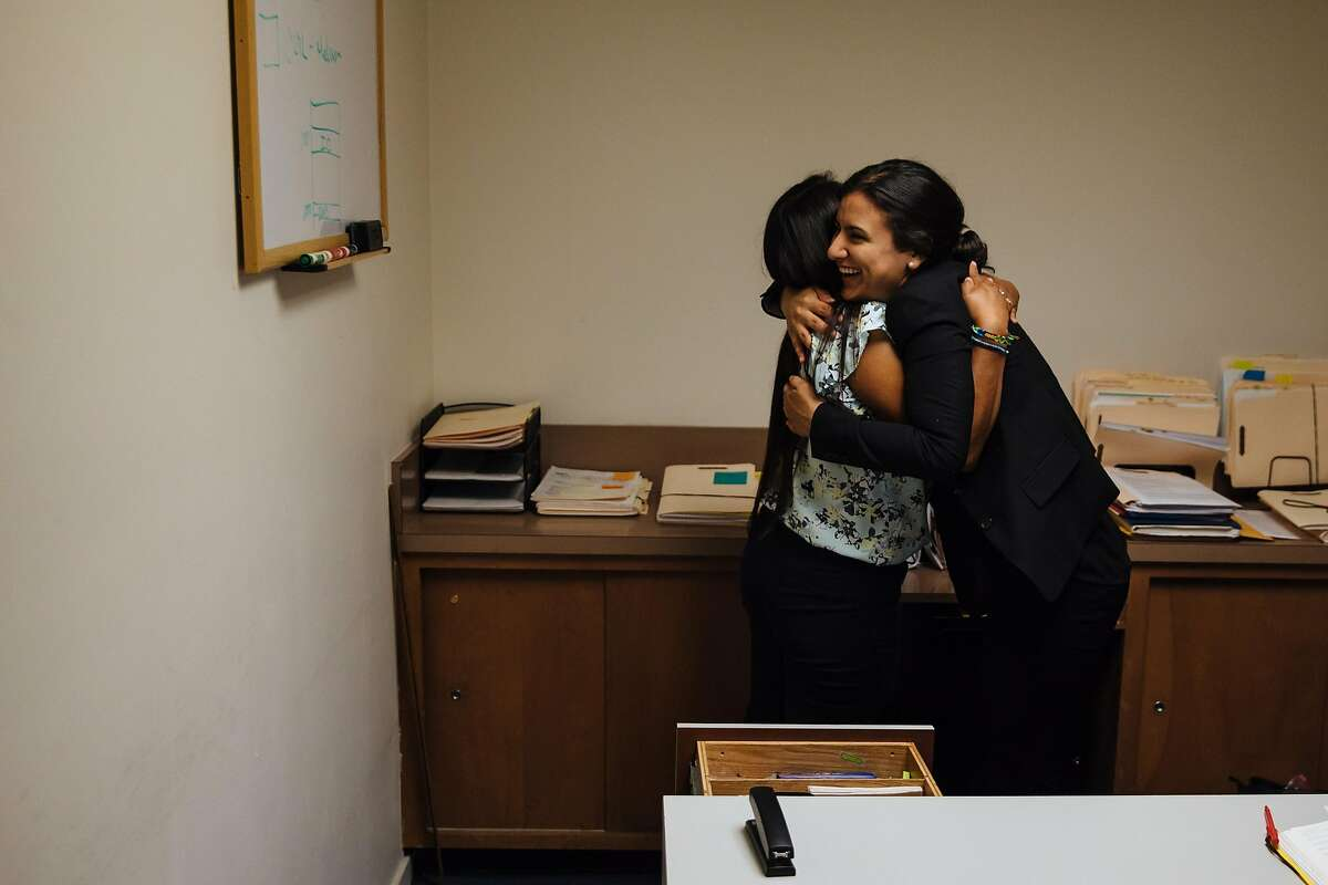 Joseline Gonzalez hugs her friend and colleague, Brenda Olivas, at Catholic Charities of the East Bay in Oakland, Calif. Thursday, August 31, 2017.