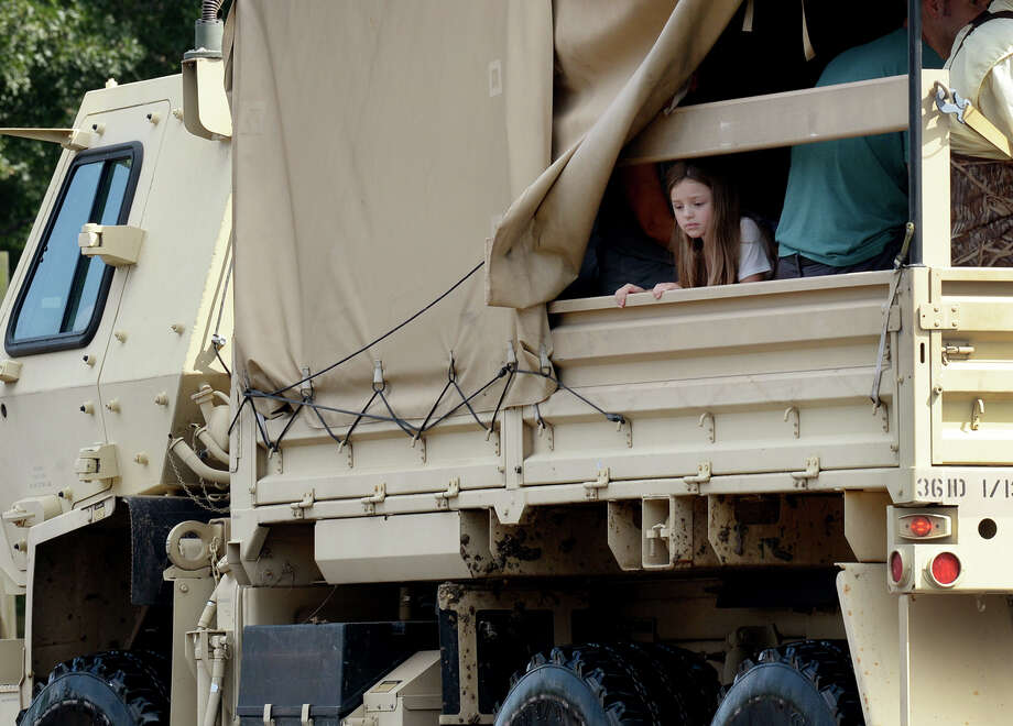 Molly Stack, 5, looks out from the back of a National Guard vehicle on Main Street in Vidor Thursday. Stack and her family were rescued from their Vidor home and said they are trying to get to family in Mississippi. Photo taken Thursday, August 31, 2017 Guiseppe Barranco/The Enterprise Photo: Guiseppe Barranco, Photo Editor / Guiseppe Barranco ©