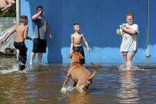 Children play with their dog in Vidor's flood waters on Main Street Thursday. Photo taken Thursday, August 31, 2017 Guiseppe Barranco/The Enterprise