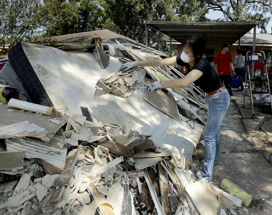 Lucy Liu dumps trash on a pile of debris as she helps her co-worker Tianna Oliver clean out her flood-damaged house. Photo: Charlie Riedel, Associated Press