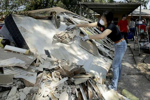 Lucy Liu dumps trash on a pile of debris as she helps her co-worker Tianna Oliver clean out her flood-damaged house Thursday, Aug. 31, 2017, in Houston. The city continues to recover from record flooding caused by Hurricane Harvey. (AP Photo/Charlie Riedel)