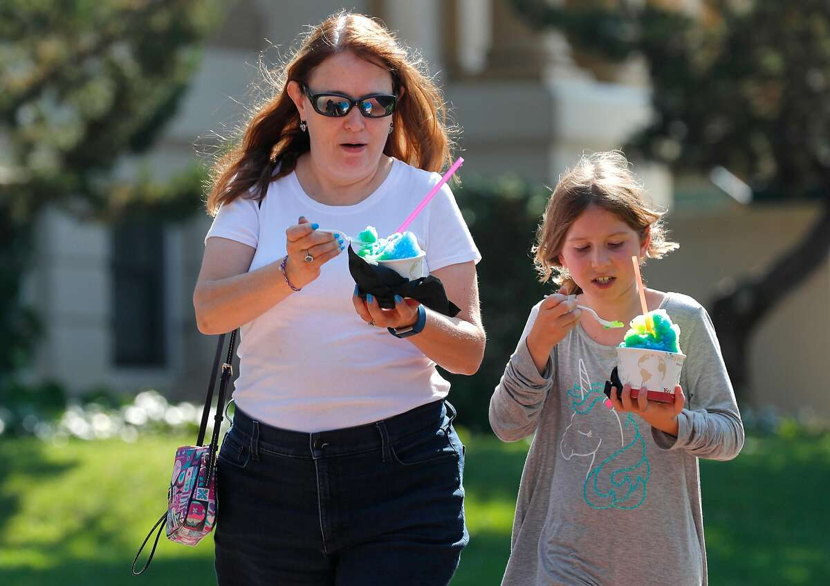 Kara Simone and her daughter Sophia, of Pleasanton enjoy a cold shave ice from the weekly farmer's market in downtown Livermore, Ca. on Thurs. August 31, 2017.