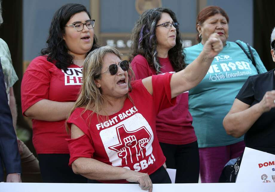 """Araceli Herrera (center, arm raised) leads a chant Thursday August 31, 2017 in front of the John Wood Federal Courthouse on East Ceasar Chavez Boulevard after U.S. District Court Judge Orlando Garcia halted most of Texas' ban on sanctuary cities Wednesday — two days before the law was to take effect. In his ruling, U.S. District Judge Orlando Garcia halted penalties for officials who endorse policies in violation of Senate Bill 4, saying it likely violates the First Amendment. SB 4 allows the attorney general to fine or remove from office local officials who """"adopt, enforce, or endorse a policy under which the entity or department prohibits or materially limits the enforcement of immigration laws."""" The law also creates penalties for local officials who block police from asking about immigration status. Photo: John Davenport, STAFF / San Antonio Express-News / ©John Davenport/San Antonio Express-News"""