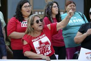 """Araceli Herrera (center, arm raised) leads a chant Thursday August 31, 2017 in front of the John Wood Federal Courthouse on East Ceasar Chavez Boulevard after U.S. District Court Judge Orlando Garcia halted most of Texas' ban on sanctuary cities Wednesday — two days before the law was to take effect. In his ruling, U.S. District Judge Orlando Garcia halted penalties for officials who endorse policies in violation of Senate Bill 4, saying it likely violates the First Amendment. SB 4 allows the attorney general to fine or remove from office local officials who """"adopt, enforce, or endorse a policy under which the entity or department prohibits or materially limits the enforcement of immigration laws."""" The law also creates penalties for local officials who block police from asking about immigration status."""
