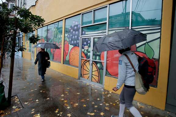 Pedestrians pass the former Real Food company which has been closed for years Tuesday December 2, 2014. A San Francisco, Calif. store on 24th Street that has been shuttered for 11 years will soon be the site of a new retail venture thanks in part to Carol Yenne who owns a store up the street.