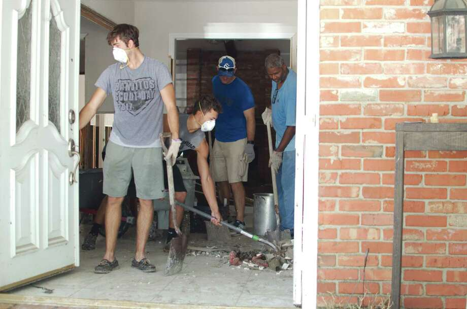 Clear Springs football players Michael Gillaspia and James Johnson assist with the cleanup with Clear Springs football coaches Daniel Stuckey and Conan Terry at the home of former CCISD Athletic Director Bill Daws in League City in the aftermath of Hurricane Harvey Thursday, Sept. 1. Photo: Kirk Sides / © 2017 Kirk Sides / Houston Chronicle