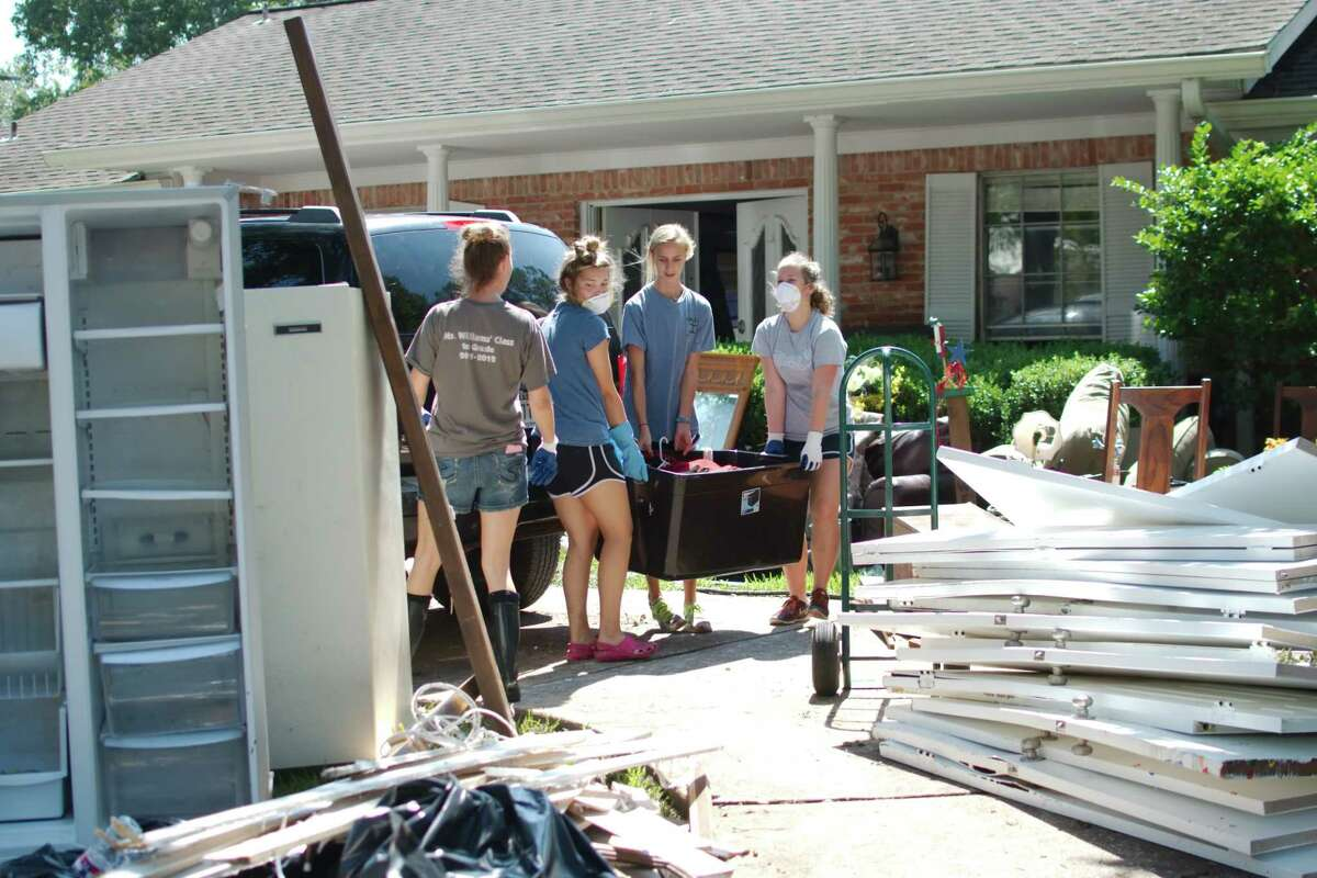 Clear Springs volleyball players Oceana Lew, Keri Spitler and Madison Williams helps with the cleanup at the home of former Clear Creek ISD Athletic Director Bill Daws in League City in the aftermath of Hurricane Harvey.