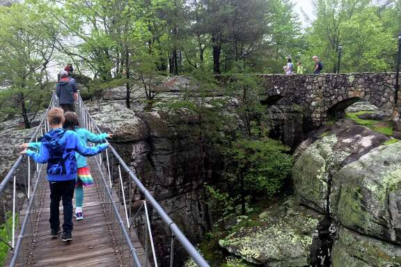 People cross the Swing-A-Long bridge at Rock City, which opened as a tourist attraction in 1932. In the background, for a more stable walk across the gorge, is the Stone Bridge.