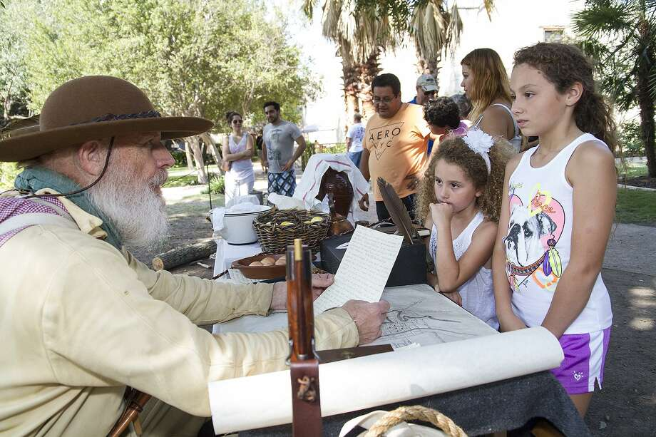 Seth Thomas reads a letter to sisters Valentina Miller, 6, and Natalie Miller, 9, (far right) as part of Fall at the Alamo, an annual interactive living history event with Alamo living history staff and volunteers, Oct. 10, 2015. Photo: Express-News File Photo / San Antonio Express-News