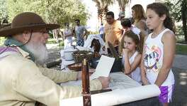 Seth Thomas reads a letter to sisters Valentina Miller, 6, and Natalie Miller, 9, (far right) as part of Fall at the Alamo, an annual interactive living history event with Alamo living history staff and volunteers, Oct. 10, 2015.