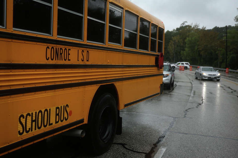 In this photo, a Conroe ISD bus stands by to take evacuees from Timber Lakes/Timber Ridge subdivision to St. Simon and Jude Catholic Church on Sunday, Aug. 27, 2017.  School buses will again be used for transporting students when schools resume on Tuesday.  (Michael Minasi / Chronicle) Photo: Michael Minasi, Staff Photographer / © 2017 Houston Chronicle