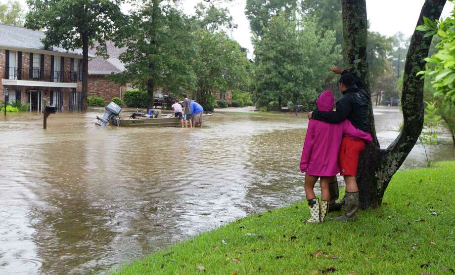 River Plantation residents watch as volunteers work through the subdivision to rescue people from high water, Monday in Conroe. Photo: Jason Fochtman, Staff Photographer / Internal