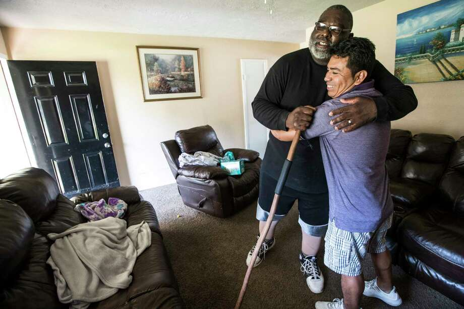 Boyd Jones, left, embraces his neighbor, Manuel Rosales on Thursday after the latter took him into his home when Jones was flooded out in the Verde Forest subdivision.  Photo: Brett Coomer, Staff / © 2017 Houston Chronicle