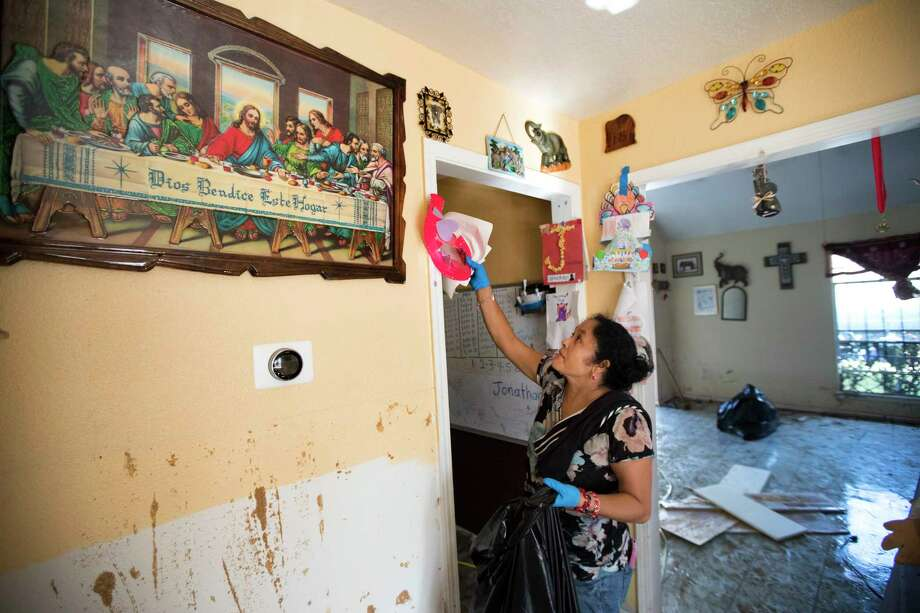 Alma Castanda pulls her children's artwork off the walls as she cleans up her flood-damaged home in the Verde Forest subdivision days after Hurricane Harvey. Photo: Brett Coomer, Houston Chronicle / © 2017 Houston Chronicle