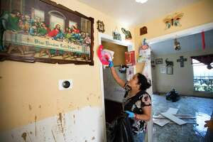 Alma Castanda pulls her children's artwork off the walls as she cleans up her flood-damaged home in the Verde Forest subdivision days after Hurricane Harvey.