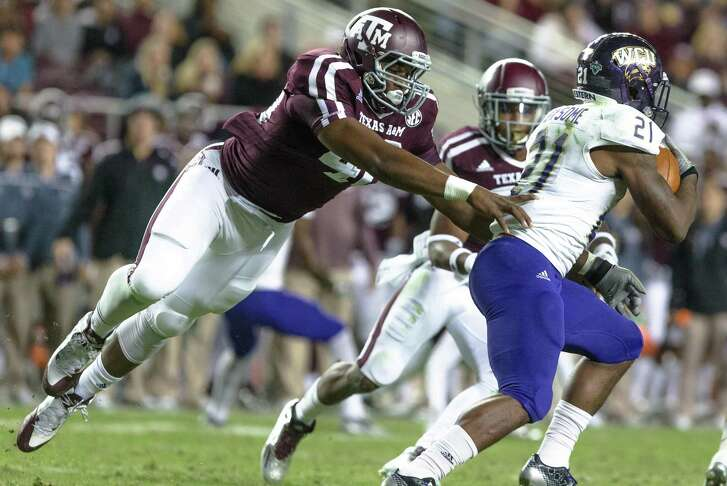 Texas A&M defensive end Jarrett Johnson puts pressure on Western Carolina's Detrez Newsome during the first half on Nov. 14, 2015, in College Station.