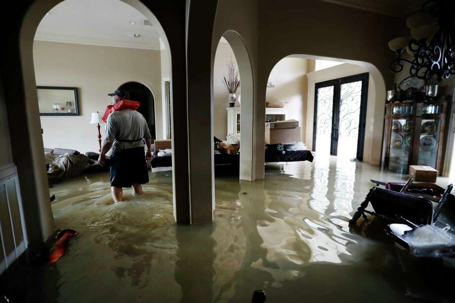 Mike Stamps stands in his home in the Kingwood Greens Subdivision flooded from the San Jacinto River due to Tropical Storm Harvey, Wednesday, Aug. 30, 2017, in Kingwood, Texas. Stamps was there to retrieve his two cats , who had to be left behind, as he was evacuated on a jet ski Tuesday. (Karen Warren/Houston Chronicle via AP) Photo: Karen Warren, MBO / @ 2017 Houston Chronicle