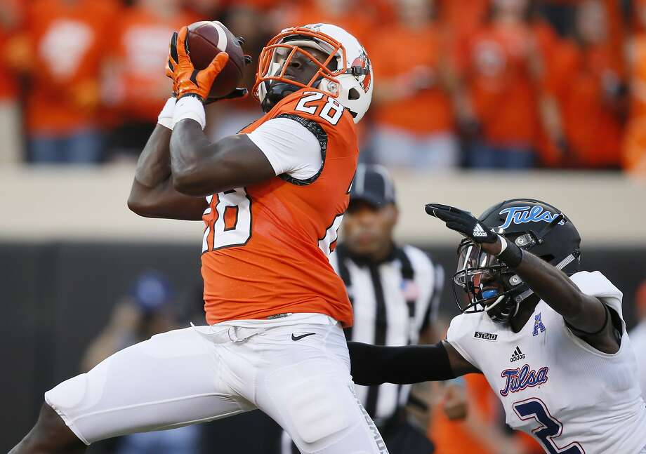 Oklahoma State wide receiver James Washington (28) catches a pass for a touchdown, in front of Tulsa cornerback Kerwin Thomas (2) during the first half of an NCAA college football game in Stillwater, Okla., Thursday, Aug. 31, 2017. (AP Photo/Sue Ogrocki) Photo: Sue Ogrocki, Associated Press