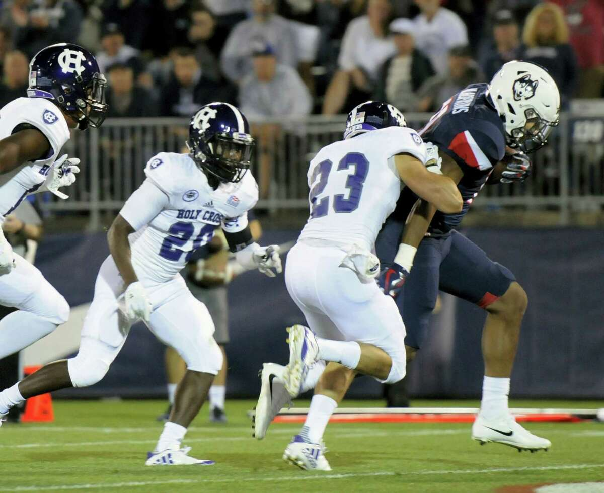 Connecticut running back Nate Hopkins, right, scores in the second quarter of an NCAA college football game against Holy Cross, Thursday in East Hartford, Conn.