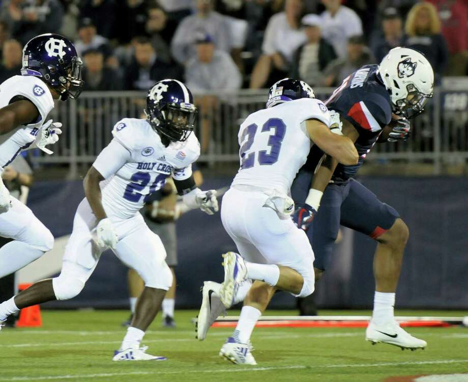 Connecticut running back Nate Hopkins, right, scores in the second quarter of an NCAA college football game against Holy Cross, Thursday in East Hartford, Conn. Photo: Stephen Dunn — The Associated Press / FR171426 AP