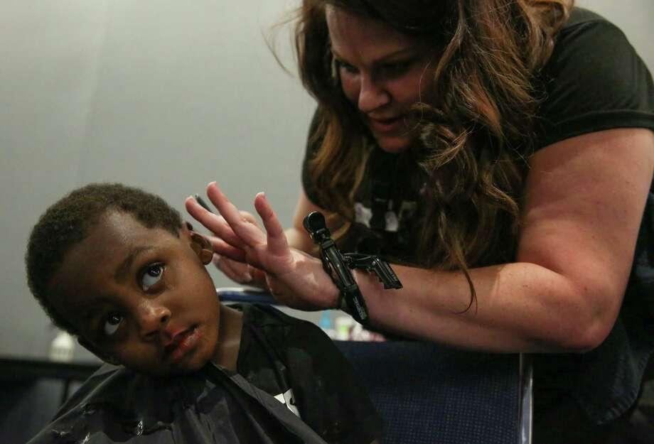 Damarcus Dosie, 2,  of Fifth Ward, gets a haircut by hairstylist Melanie Jones at George R Brown Convention Center on Thursday, August 31, 2017, in Houston. About 50 hairstylists volunteered to provide hair services to Hurricane Harvey flood evacuees. Photo: Yi-Chin Lee / Houston Chronicle, Yi-Chin Lee / Houston Chronicle 2017