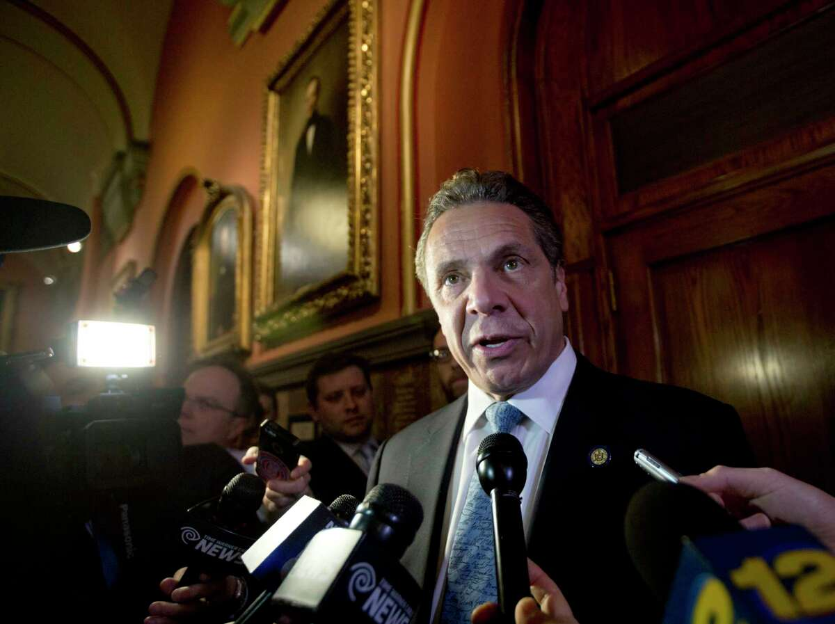 New York Gov. Andrew Cuomo talks to media members outside his office at the state Capitol on Wednesday, March 30, 2016, in Albany, N.Y. Cuomo says legislative leaders have agreed to a $150 billion state budget plan that includes a minimum wage hike and $1 billion in middleclass income tax relief. (AP Photo/Mike Groll) ORG XMIT: NYMG107